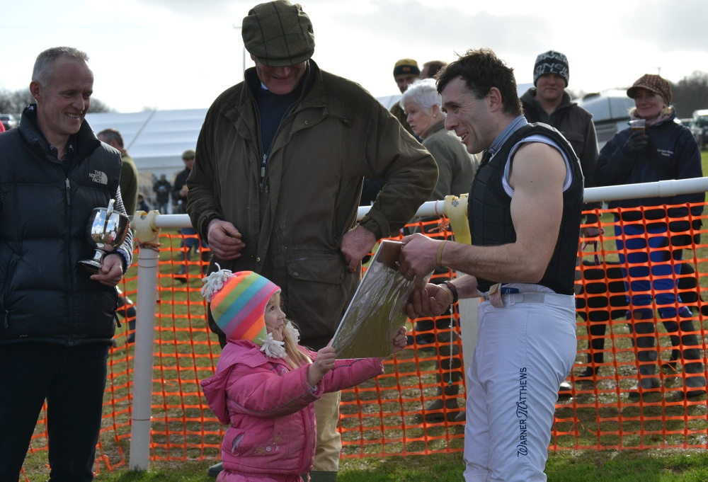 Xaviera Wall presents dad Mark with a print after his win in the Mens Open