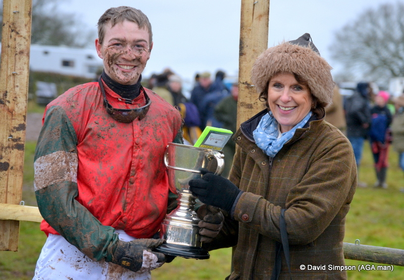 A muddy Fred Timmis receives his trophy from Caroline Robinson after winning the PPORA Club Members race for Novice Riders